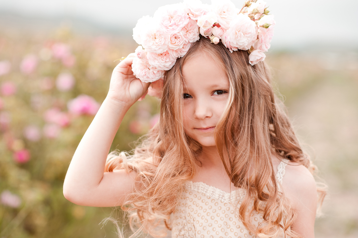 Smiling baby girl wearing wreath with roses outdoors. Looking at camera. Childhood. Summer time.